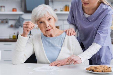ältere Frau zeigt Puzzleteil, während Krankenschwester ihre Schulter berührt