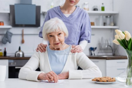 Photo for Young nurse touching shoulders of elderly woman looking at camera near jigsaw puzzle - Royalty Free Image