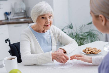 Photo for Elderly woman playing jigsaw puzzle with social worker on blurred foreground - Royalty Free Image