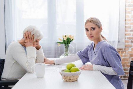 enfermera joven mirando a la cámara, mientras que la calma molesta mujer mayor cerca del rompecabezas