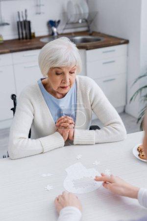 Sozialarbeiter zeigt auf Puzzle nahe Seniorin zu Hause
