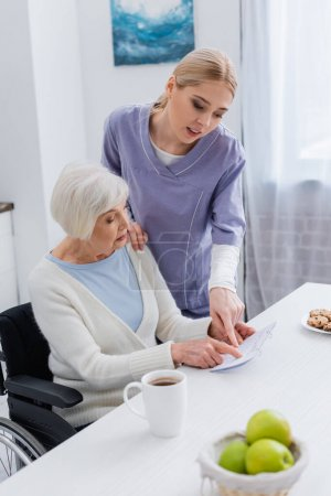 Photo for Social worker pointing at calendar near elderly woman sick on dementia - Royalty Free Image