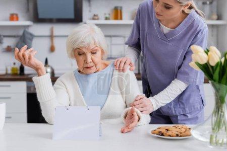 Photo pour Jeune infirmière touchant l'épaule de la femme âgée montrant geste haussement d'épaules près du calendrier - image libre de droit