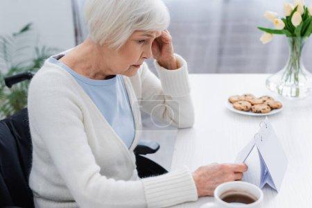 Photo pour Femme âgée, souffrant de perte de mémoire, regardant le calendrier à la maison - image libre de droit
