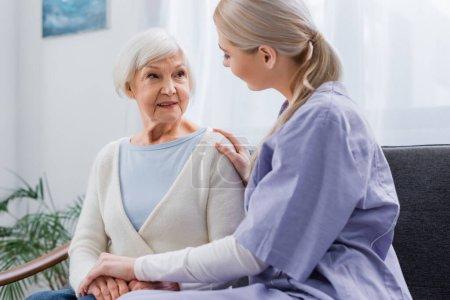 Sozialarbeiter berührt Seniorin beim Gespräch zu Hause an den Händen