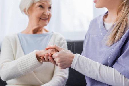 nurse holding hand of aged woman smiling on blurred background