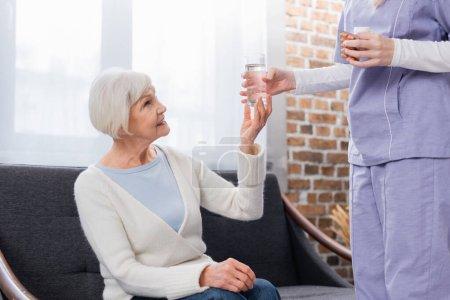 Photo pour Travailleur social tenant des pilules tout en donnant un verre d'eau à une femme âgée souriante - image libre de droit