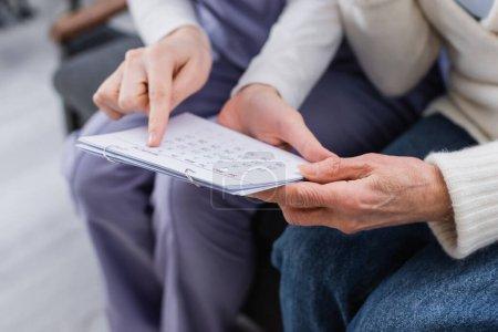 Photo pour Vision partielle du travailleur social pointant du doigt un calendrier proche d'une femme âgée malade d'amnésie - image libre de droit
