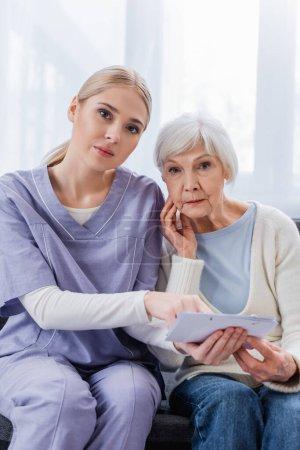 Photo pour Jeune infirmière et femme âgée, malade de démence, regardant la caméra tout en tenant le calendrier - image libre de droit