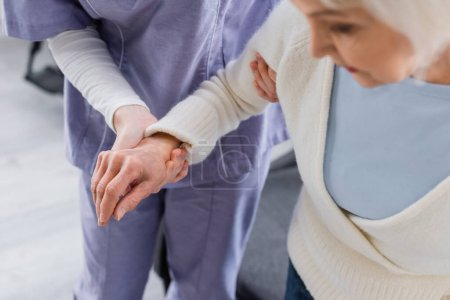 partial view of nurse supporting aged woman, blurred foreground
