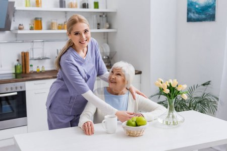 young nurse smiling at camera while embracing happy aged woman in kitchen