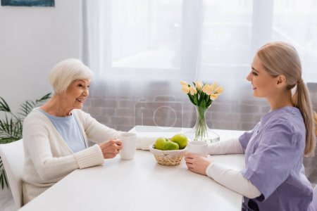 Photo for Joyful senior woman and young social worker talking in kitchen near tea and fresh apples - Royalty Free Image