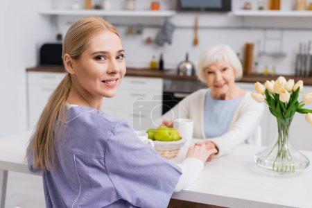 enfermera joven sonriendo a la cámara mientras se toma de la mano con la mujer mayor sobre fondo borroso
