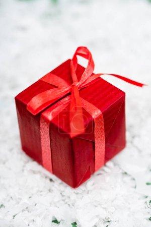 Photo pour Boîte cadeau rouge avec ruban et arc sur la surface de neige décorative - image libre de droit