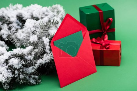 Photo for Red envelope with card near gift boxes and fir branch with decorative snow on green - Royalty Free Image