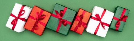 Photo for Website header of multicolored gift boxes with red ribbons and bows on green background, top view - Royalty Free Image