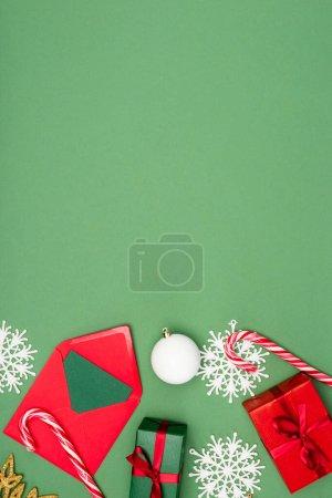 Photo pour Vue du haut de la boîte cadeau, enveloppe avec carte, boule de Noël, cannes à bonbons et flocons de neige décoratifs sur fond vert avec espace de copie - image libre de droit