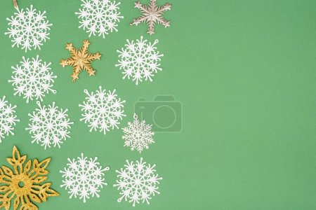 Photo for Top view of decorative white, golden and silver snowflakes on green background with copy space - Royalty Free Image
