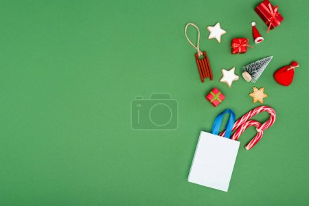 Photo for Shopping bag with candy canes, christmas baubles and cookies on green background with copy space - Royalty Free Image