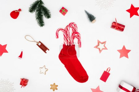 Photo for Red christmas stocking with candy canes near cookies and festive baubles on white background - Royalty Free Image