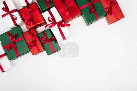 top view of colorful present boxes with red ribbons and bows on white background