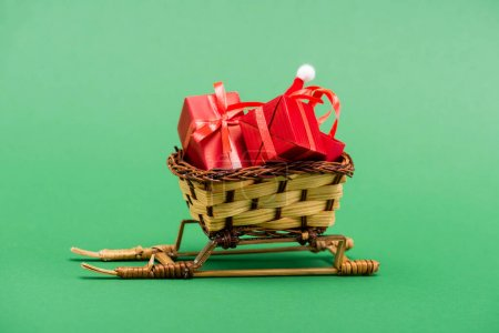 Photo for Red gift boxes and santa hat in wicker basket on decorative sleigh on green background - Royalty Free Image