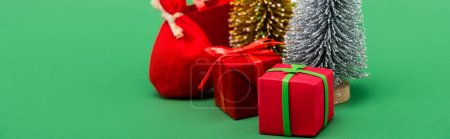 website header of decorative silver and golden christmas trees near gift boxes and sack on green