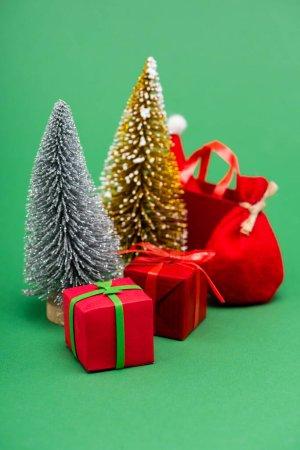 Photo pour Arbres de Noël décoratifs en argent et or près de boîtes cadeaux, sac et sac à provisions avec chapeau de Père Noël sur vert - image libre de droit