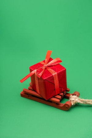 red gift box on decorative wooden sleigh on green background
