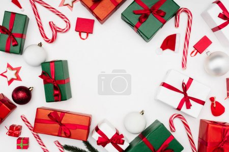 Photo for Frame of multicolored gift boxes, candy canes and christmas baubles on white - Royalty Free Image