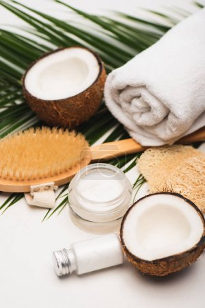 coconut halves, homemade cosmetic cream and lotion near towel, massage brush, and palm leaves on white