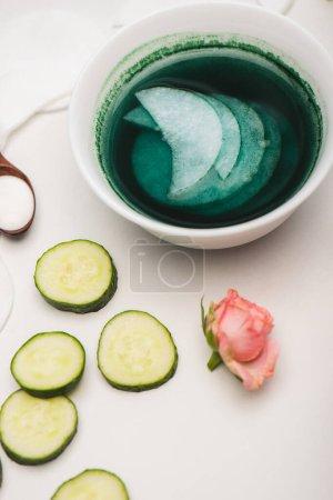 Photo pour Thé rose, tranches de concombre, bol avec lotion et tampons de coton sur la surface blanche - image libre de droit