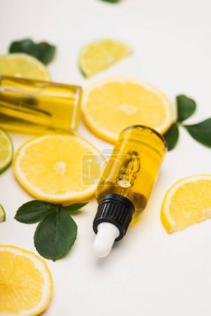 Photo pour Foyer sélectif de tranches de citron et de citron vert près de bouteilles d'huile essentielle d'agrumes et de feuilles de rose sur fond flou - image libre de droit