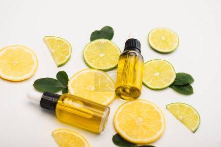 Photo pour Bouteilles avec de l'essence d'agrumes, citron frais et tranches de citron vert près des feuilles de rose sur la surface blanche - image libre de droit
