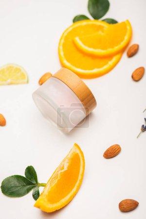 Photo pour Récipient de crème cosmétique maison près de tranches d'orange fraîche, d'amandes et de feuilles de rose sur blanc - image libre de droit