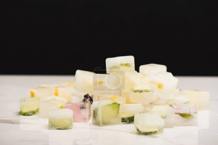 stack of fruit, vegetable and floral ice cubes on white surface isolated on black