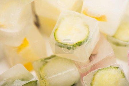 Photo pour Vue rapprochée des glaçons rafraîchissants aux légumes et fruits sur fond blanc flou - image libre de droit