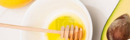 top view of bowl with honey and wooden dipper, cut avocado and fresh lemon on white, banner