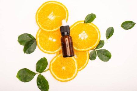 Photo pour Vue du dessus de la bouteille avec de l'huile essentielle d'agrumes et des tranches d'orange juteuses près des feuilles de rose sur blanc - image libre de droit