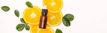 bottle of homemade citrus essence, fresh orange slices near rose leaves, banner