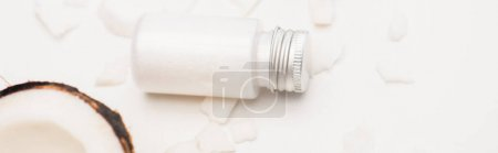 Photo for Bottle of nourishing homemade lotion near coconut half and flakes on white, banner - Royalty Free Image