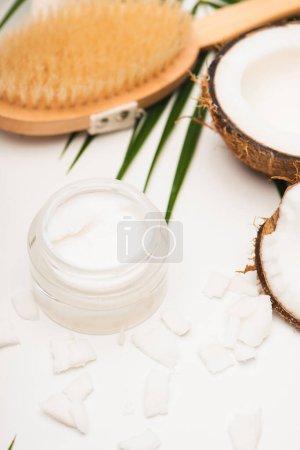 Photo pour Moitié de noix de coco et flocons près de crème cosmétique maison et brosse de massage sur fond flou - image libre de droit