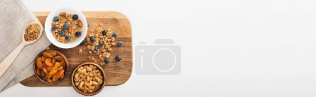 top view of delicious granola with nuts, blueberry and dried apricots isolated on white, banner