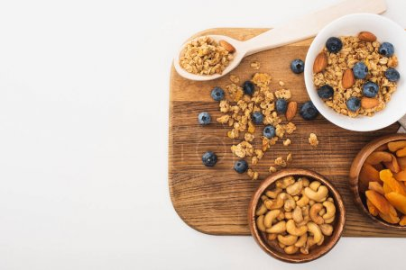 top view of delicious granola with nuts, blueberry and dried apricots isolated on white