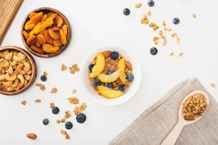 top view of delicious granola with nuts, peach, blueberry and dried apricots isolated on white