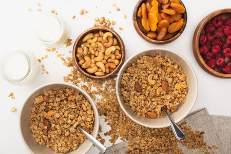 Photo for Top view of delicious granola with nuts, raspberry, yogurt and dried apricots isolated on white - Royalty Free Image