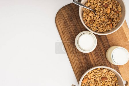 Photo for Top view of delicious granola with nuts, yogurt isolated on white - Royalty Free Image