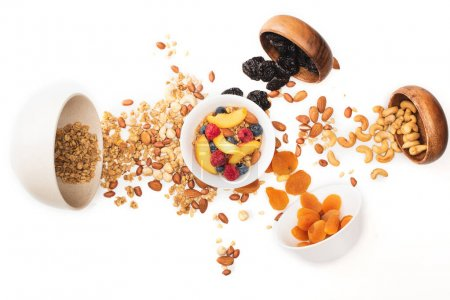 top view of delicious granola with nuts and fruits scattered from bowls isolated on white