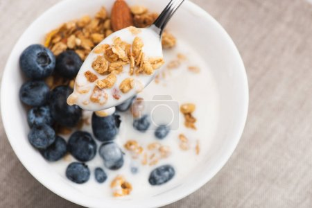 spoon with delicious granola and yogurt on blurred background
