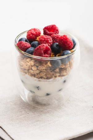 delicious granola with berries and yogurt in glass cup